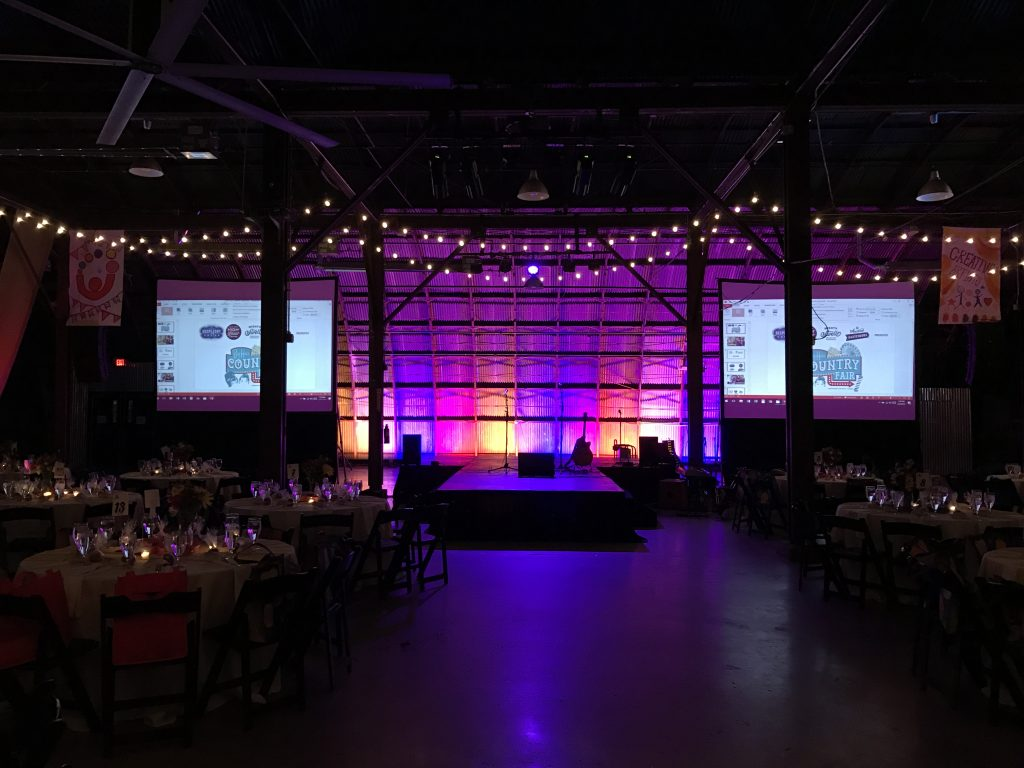 Dark performance area backlit with multicolored lights, bordered (sided) by two large projector screens