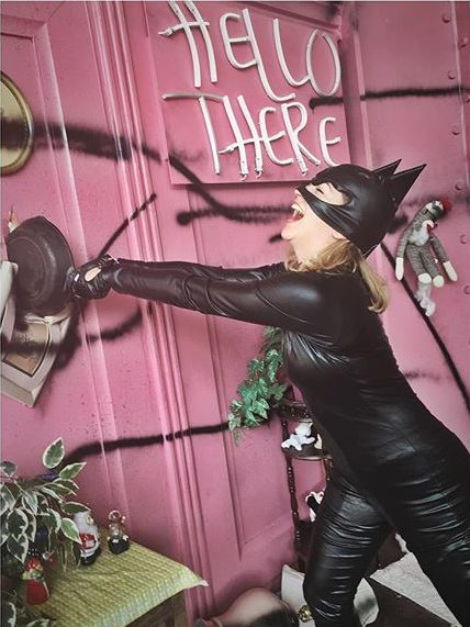 A woman dressed as Catwoman laughing as she smashes a castiron pan through a door in a pink room