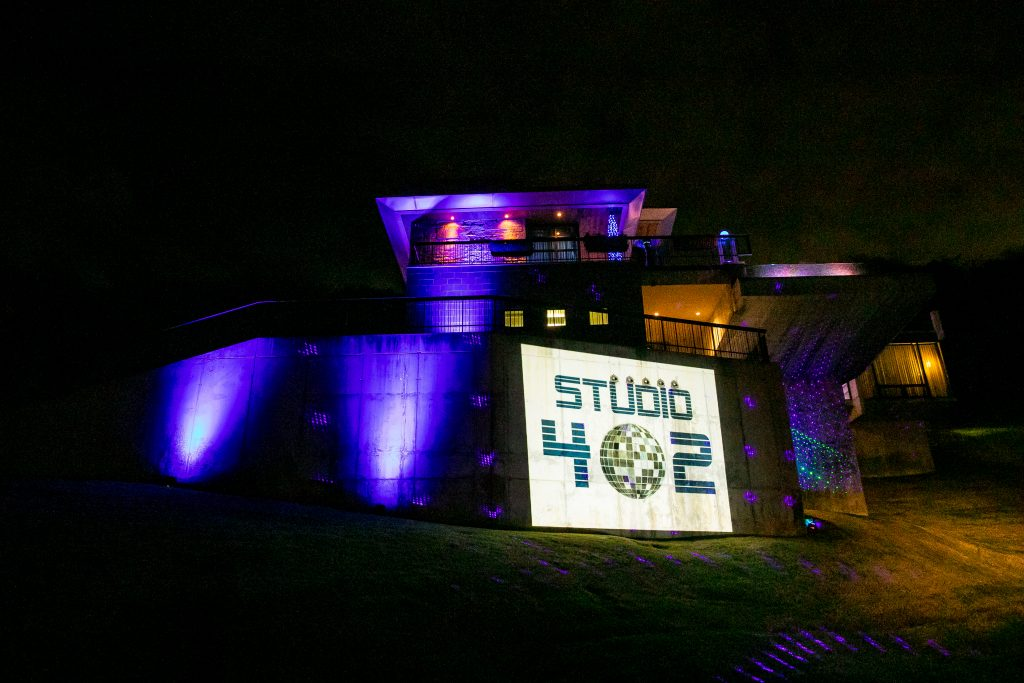 "Hillside mansion lit up in purple light with ""Studio 402"" Image displayed on the front wall"