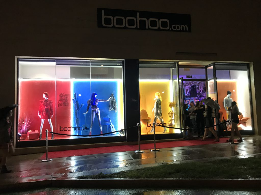 Storefront windows showcasing different colored backdrops with mannequins posed and styled to match their prospective color